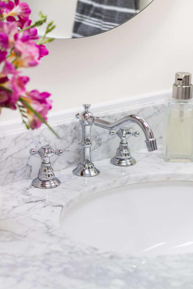 Shiny faucets on the marble vanity.