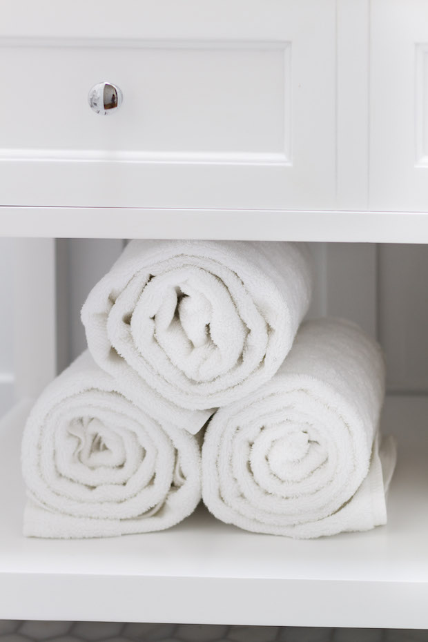 White rolled up towels in the vanity.