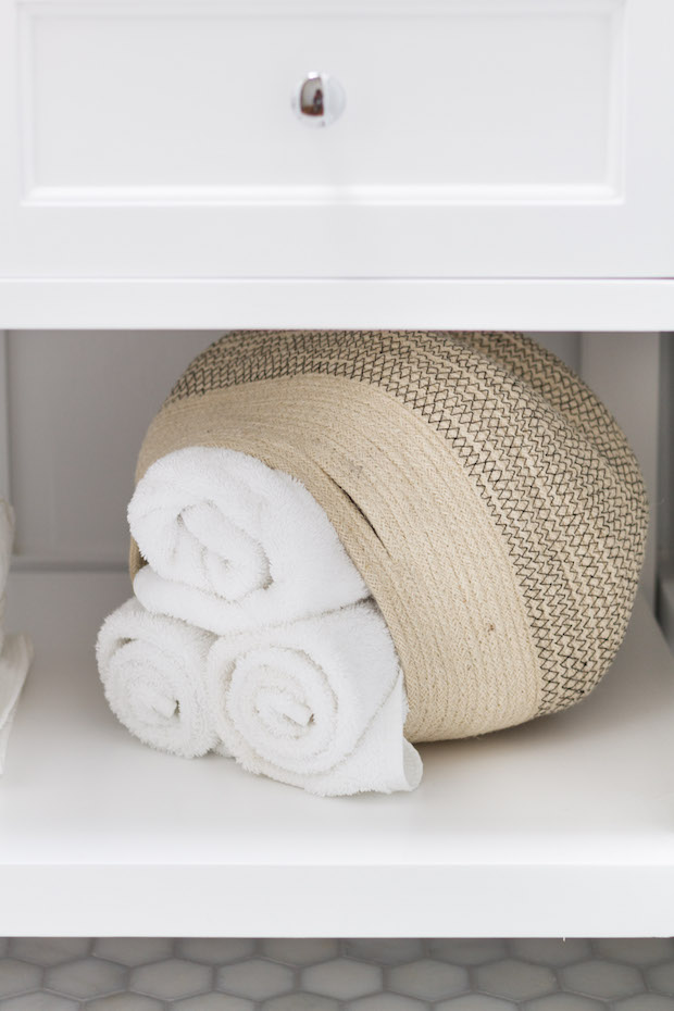 Rolled up towels in a basket on the lower shelf in the bathroom.