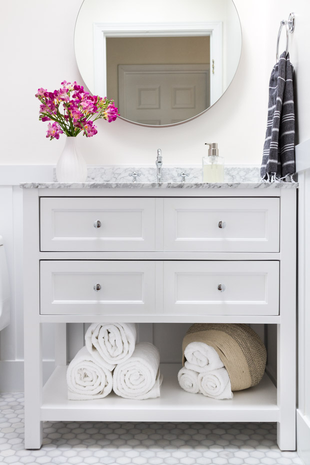 White vanity with drawers in the bathroom.