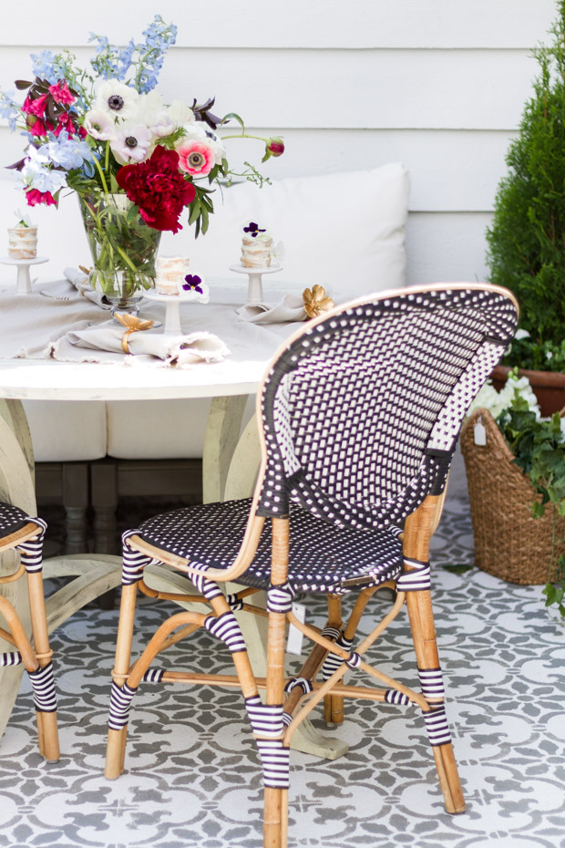 Wicker chairs on patio beside table.