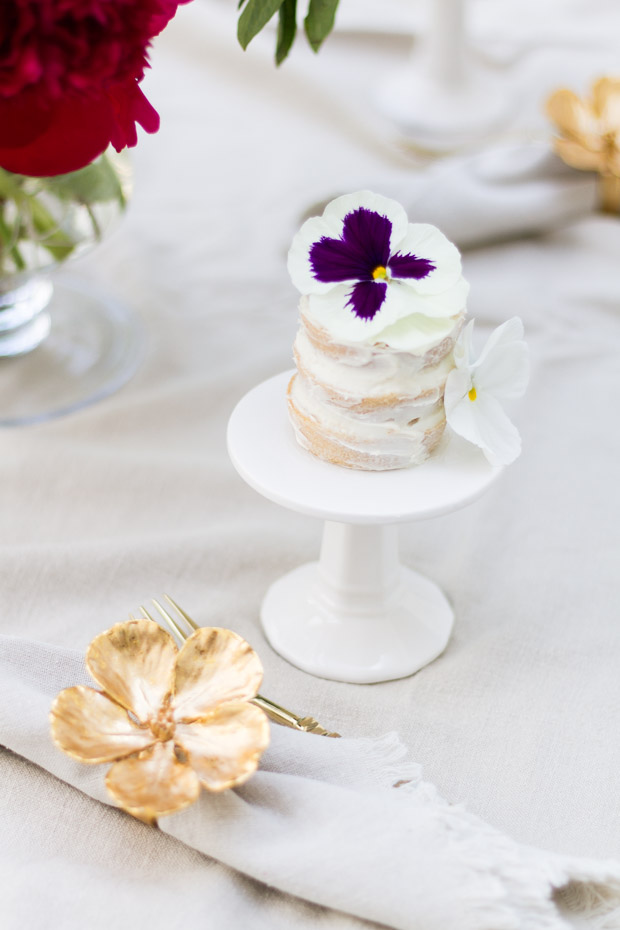 Individual mini cupcake with white and purple flower on top.