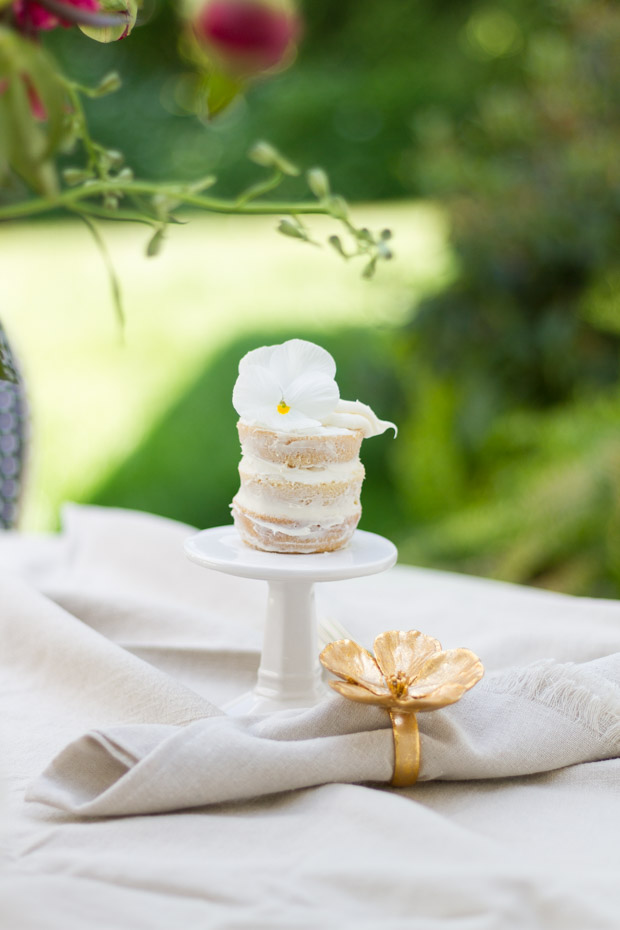 White napkin with a flower napkin holder in gold.