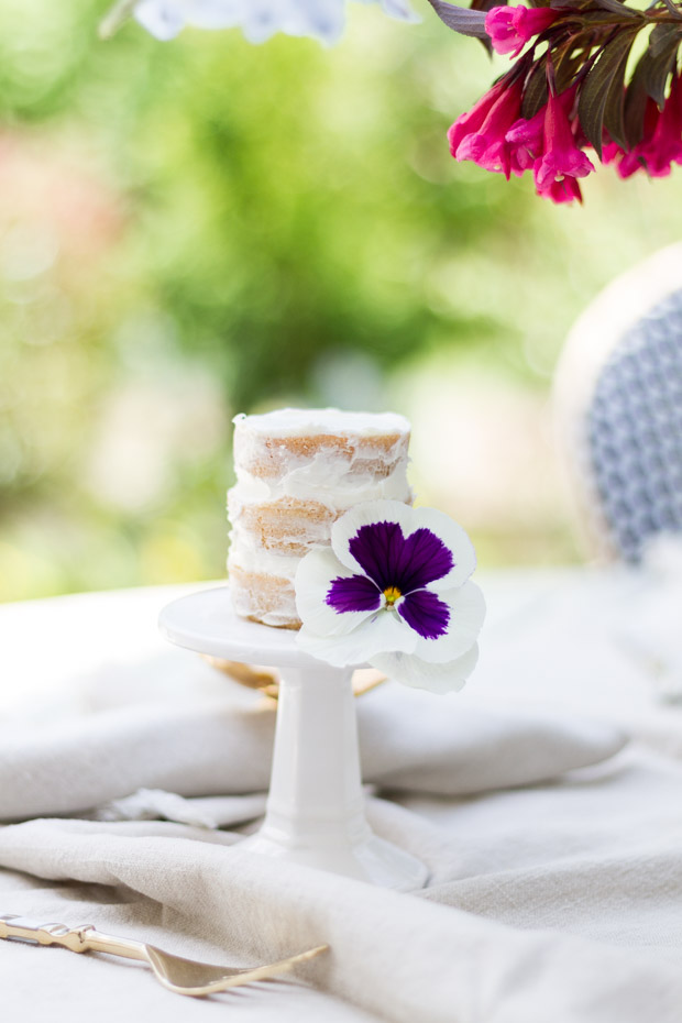 White mini cake stand with naked cake on it.