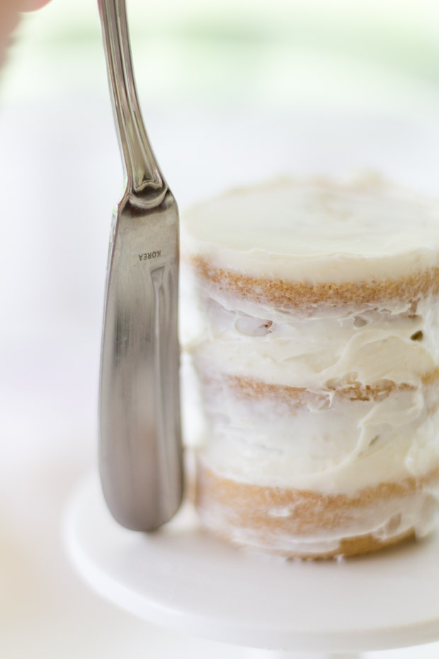 A knife smoothing out the white frosting.