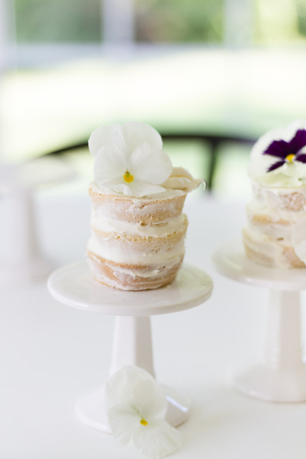 A mini naked cake with a white flower on top of it.