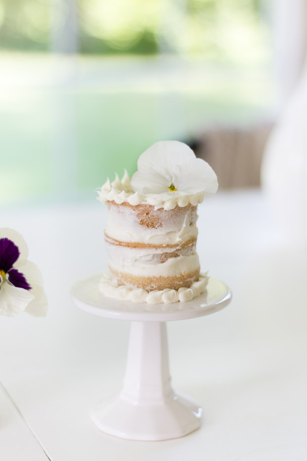 A mini naked cake with a white flower and extra piping dots around the top and bottom.
