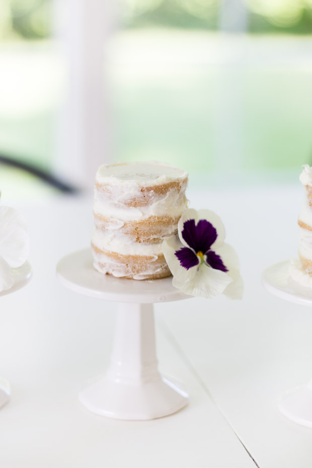 The mini naked cake on a white cake stand with a purple and white posy flower beside it.