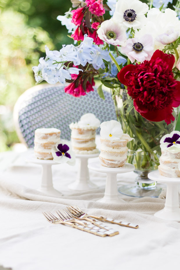 Little mini naked cakes on individual stands with red, white and pink flowers in a vase beside them.