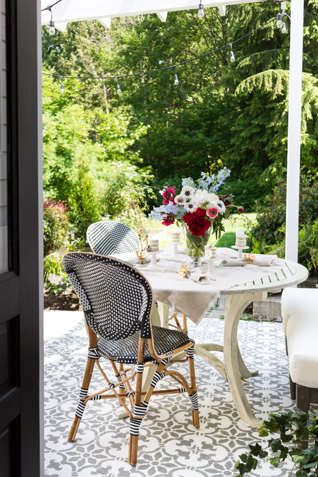 Outdoor table setting with pretty flowers in the middle.