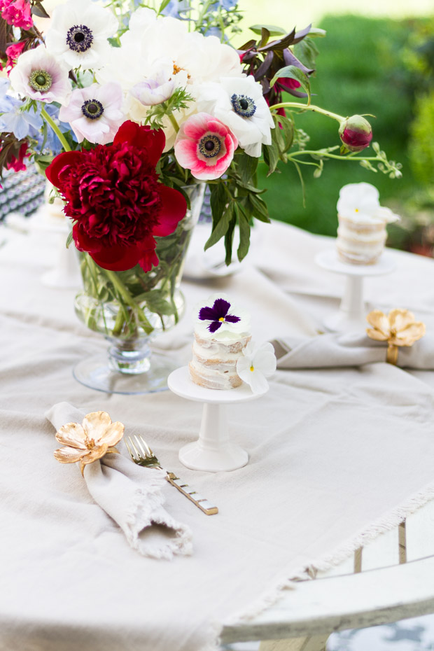 Red and white large floral bouquet in middle of white table.