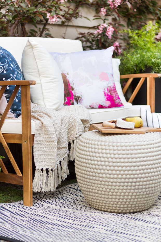 A neutral outdoor ottoman and a rug underneath it.