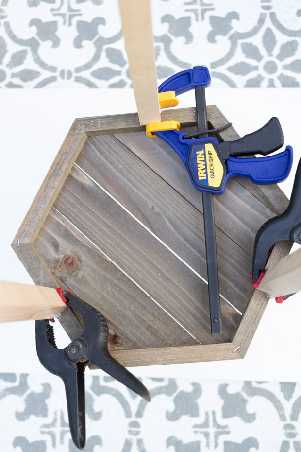 Using clamps to hold the glued pieces together.