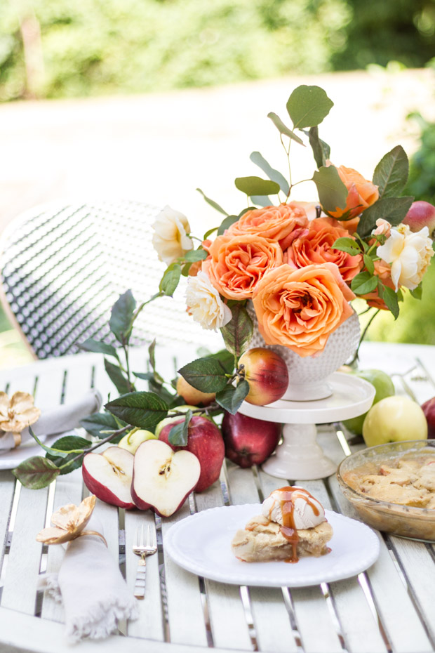 Flowers and apples with pie on plate on table.