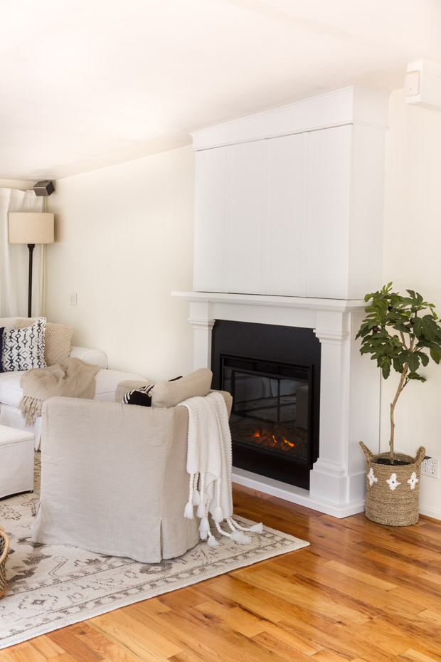 White neutral armchair in front of fireplace that is on.
