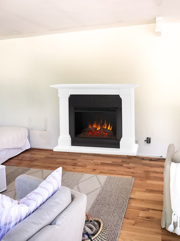 Electric fireplace with faux logs in living room.