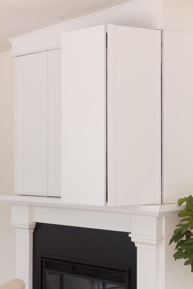 Cabinet door above fireplace ajar.