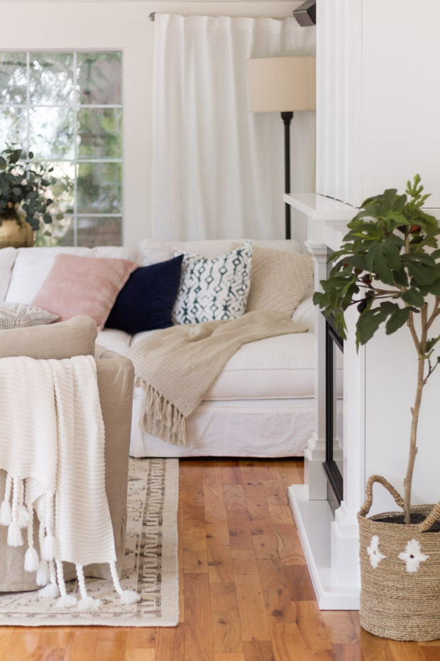 White neutral couch with pillows and blankets.