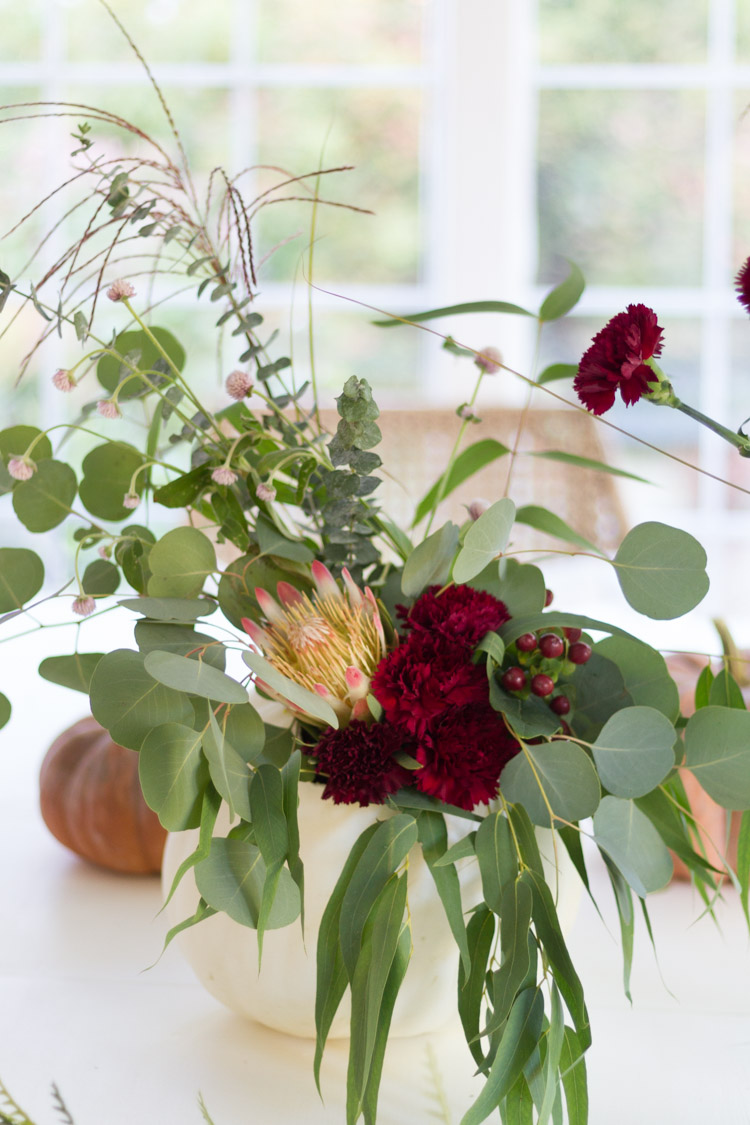 Putting in dark red carnation flowers to the arrangement.