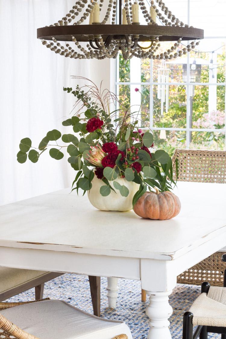 Floral pumpkin arrangement on wooden table with wooden chandelier overhead.
