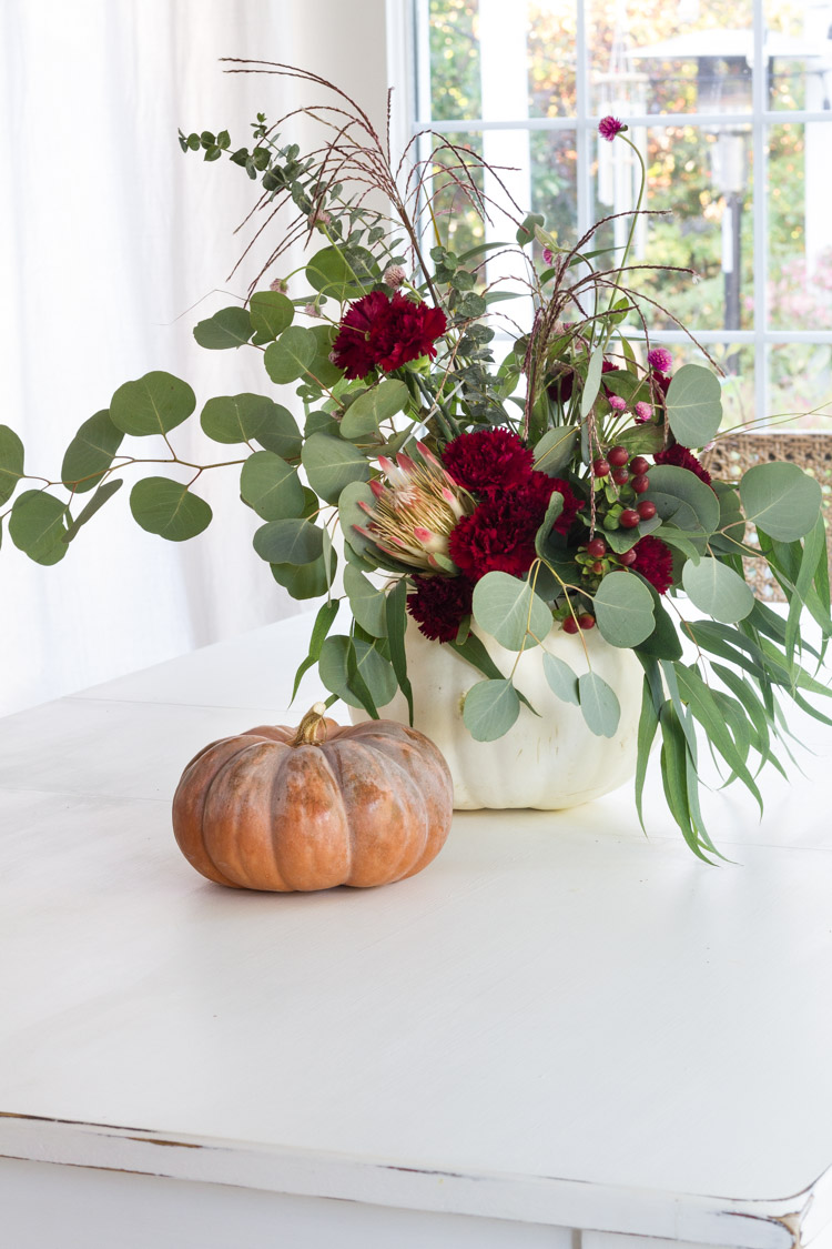 Pumpkin on counter with red flowers and greenery.