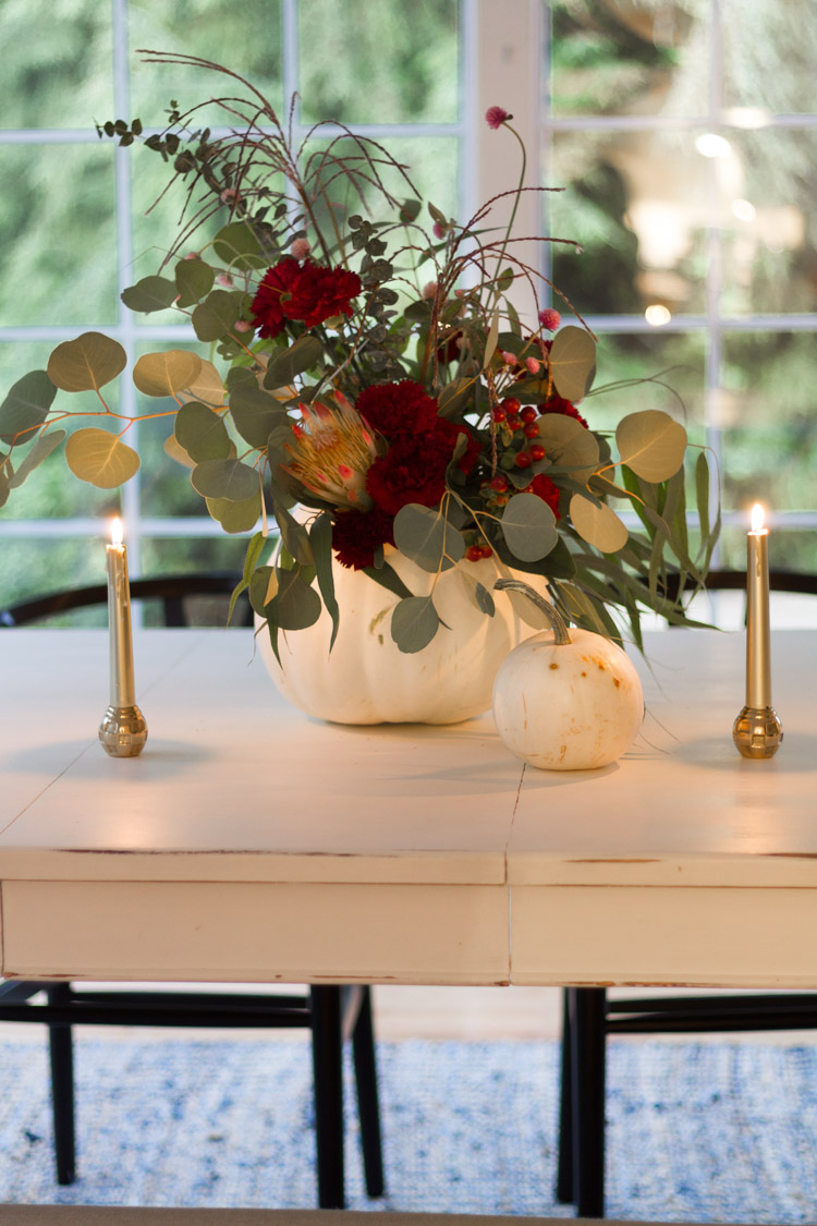 Brass candles on either side of the centerpiece.