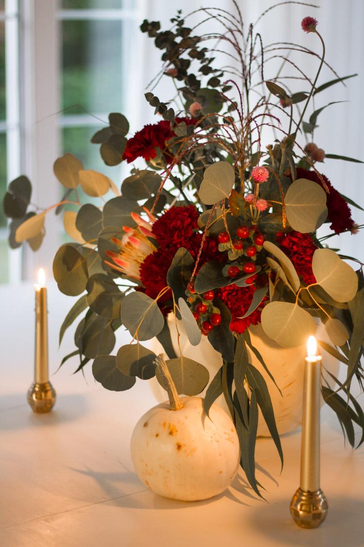 Soft glow of the candles beside the pumpkin arrangement.