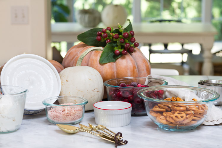 On the counter is a pumpkin with cranberries on top of it, gold spoons, pretzels and bowls.