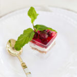 Cranberry pretzel salad with a sprig of mint leaf.