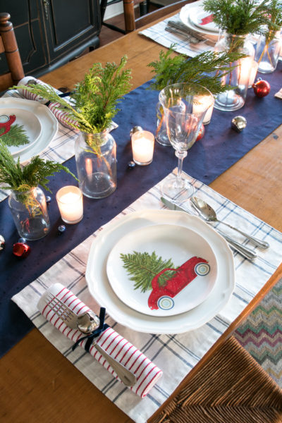 A table setting with a red truck and tree on the plate.