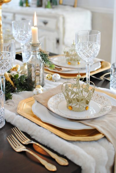 White plates, gold cutlery and a crown on a plate on the table.