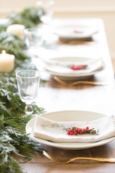 Greenery, and candles plus white plates with napkins on them.