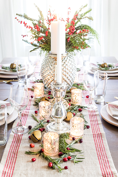 Lots of lit candles, and wine glasses, plus a table runner on decorated holiday table.