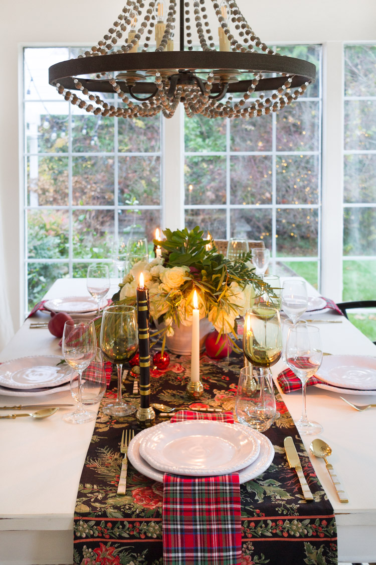 Lit candles, a holiday table runner and white plates on the table.