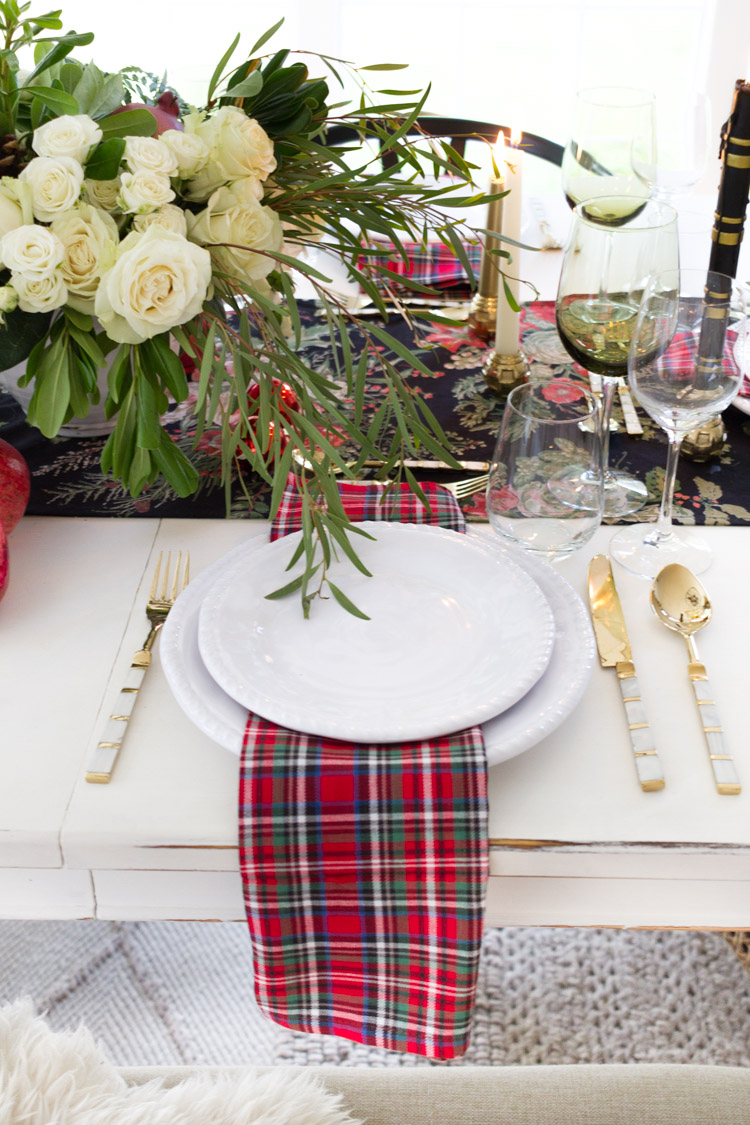 Plaid table runner, white plates, gold and white cutlery and white roses on the table.