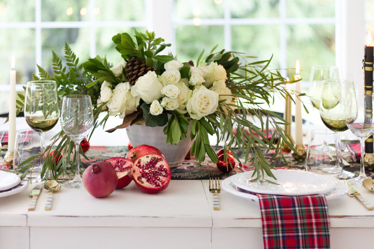 White floral table arrangement, and half a pomegranate on the table.