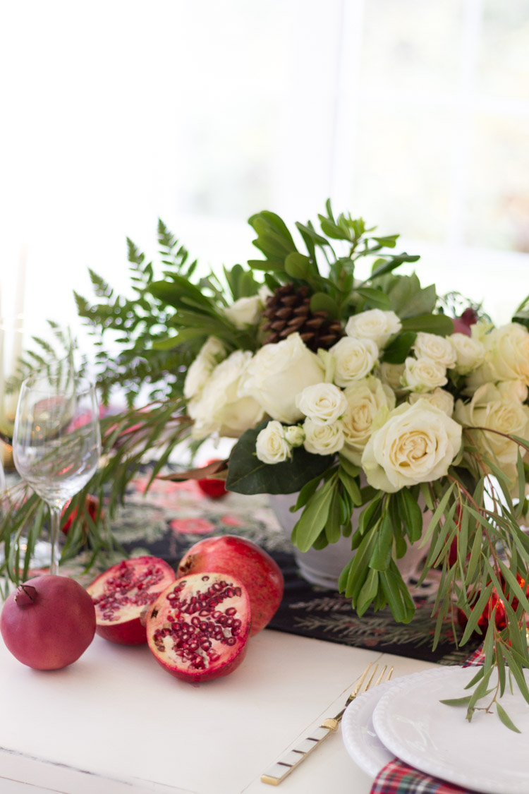 White roses, a pomegranate and wine glasses on the table.
