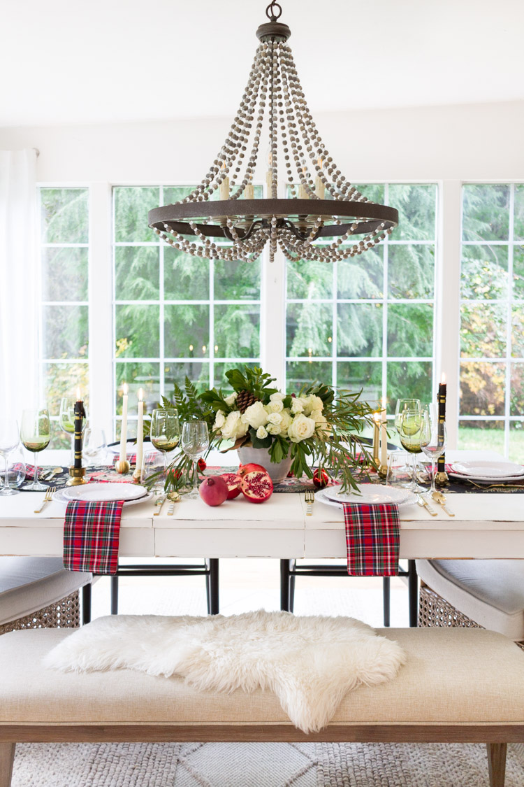 Wooden beaded chandelier, a bench with faux fur, plaid and a pomegranate cut in half on the table.