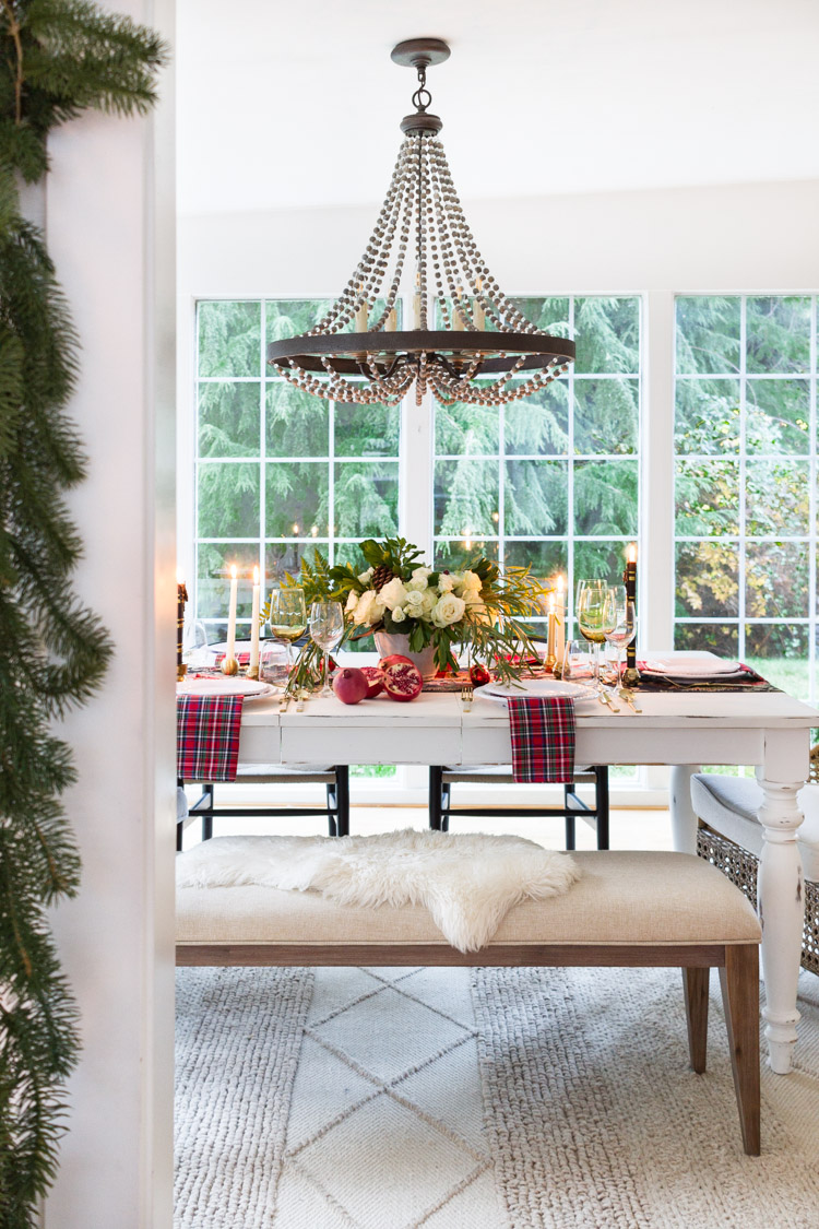 A decorated styled and set Christmas table with a large window behind the table.