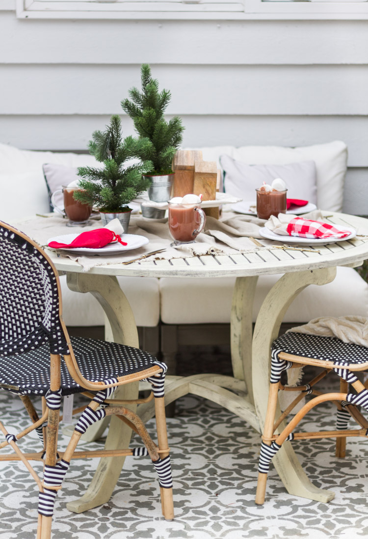A decorated outdoor table with black and white wicker chairs surrounding it.