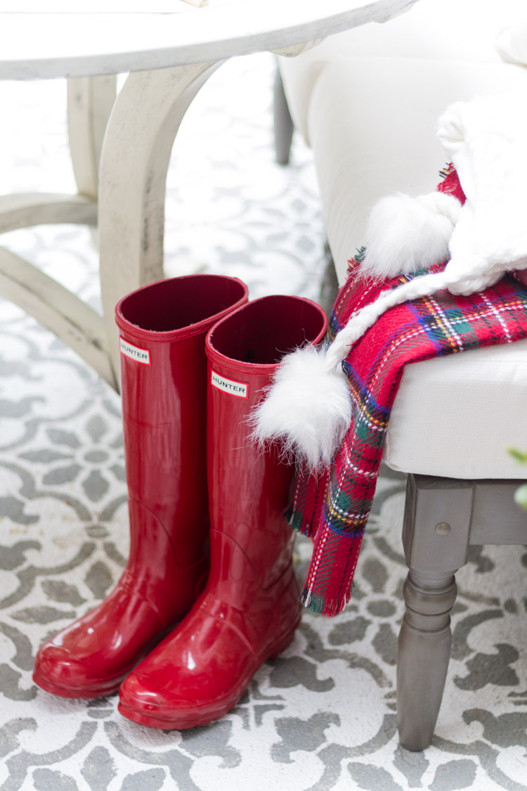 Red rubber boots beside the table with a red plaid blanket beside them.