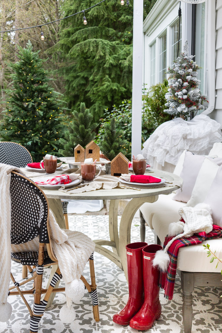 An outdoor table setting with red gum boots beside the chair.