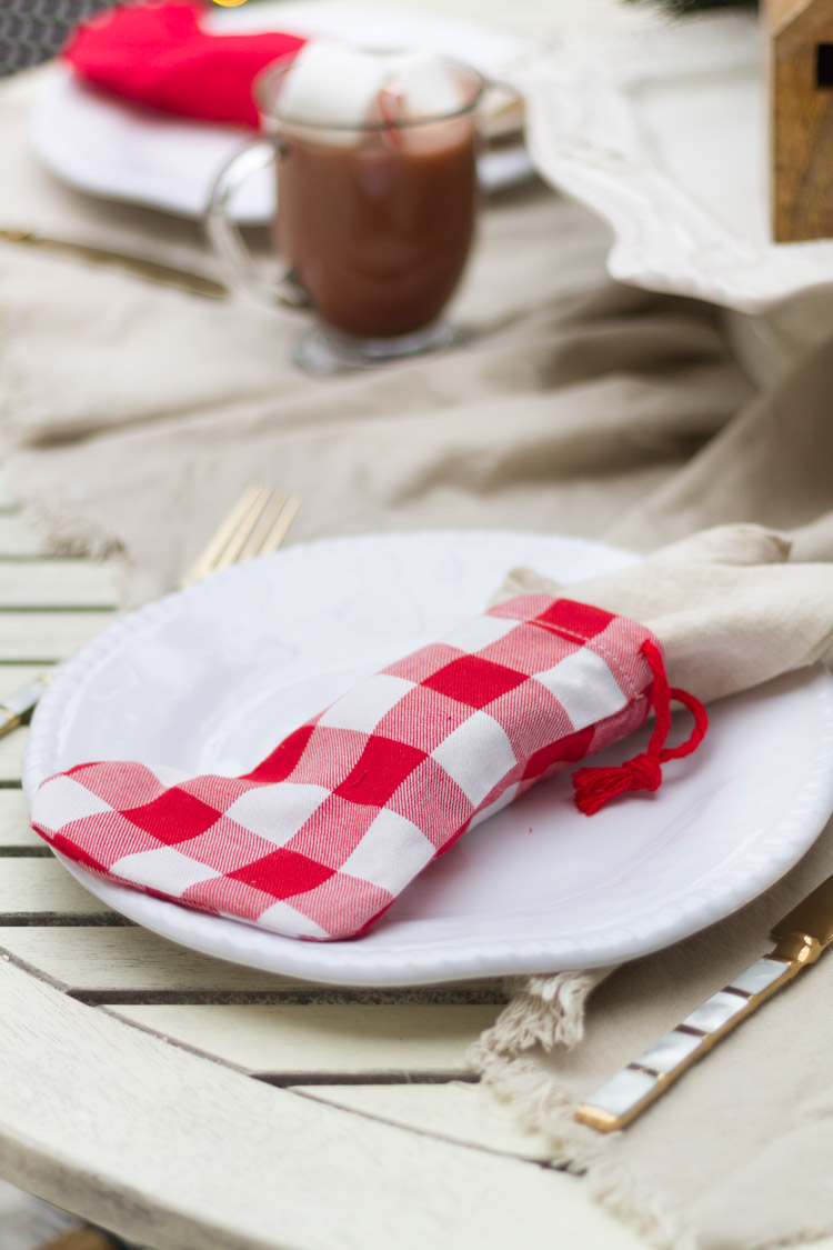 Red and white chekered stockings as napkin holders on the white plates.