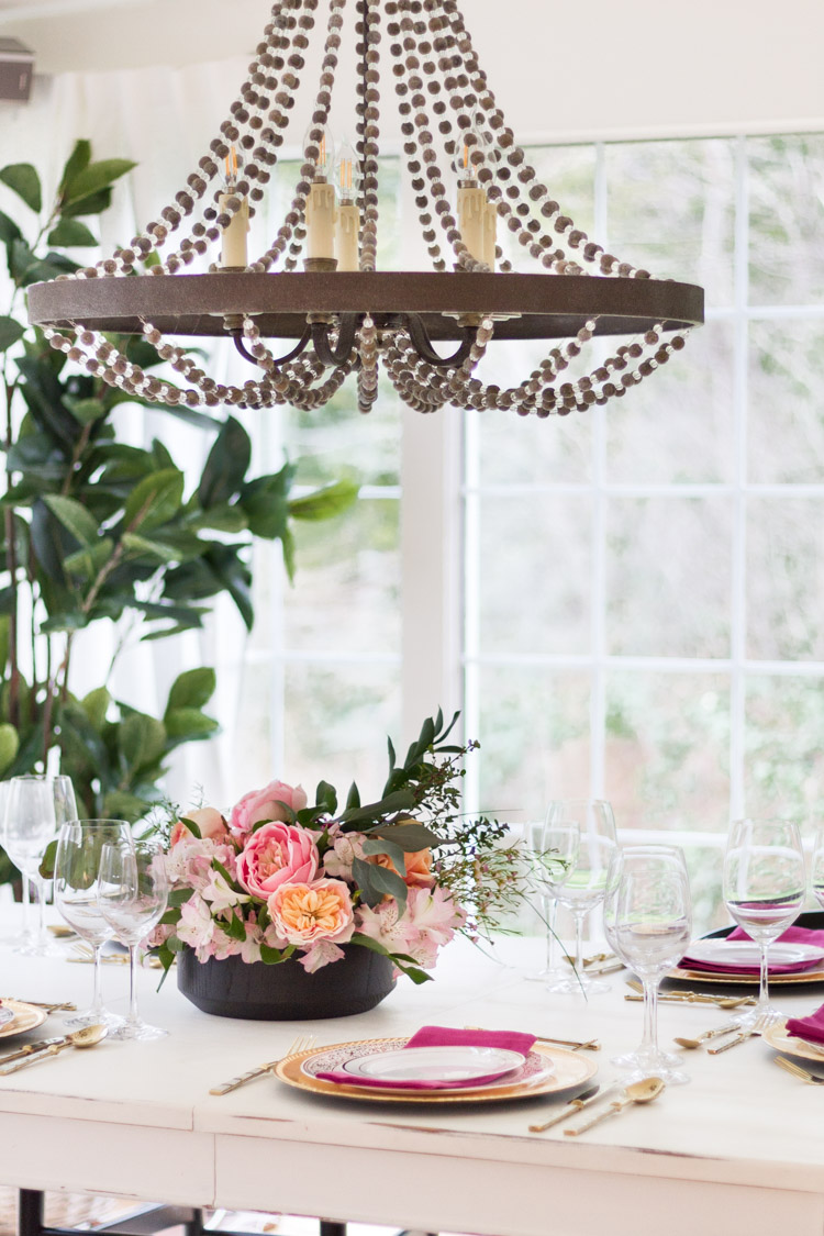 A wooden beaded chandelier above the table.