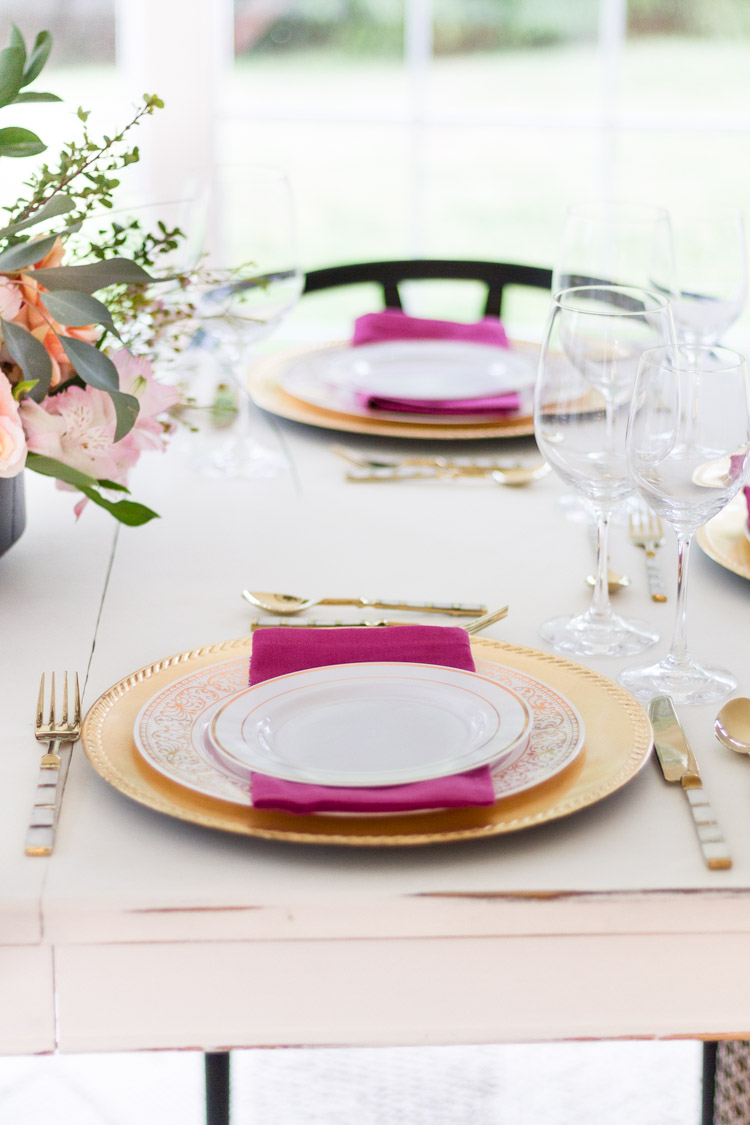 Gold chargers, white plates and pink napkins on the table.
