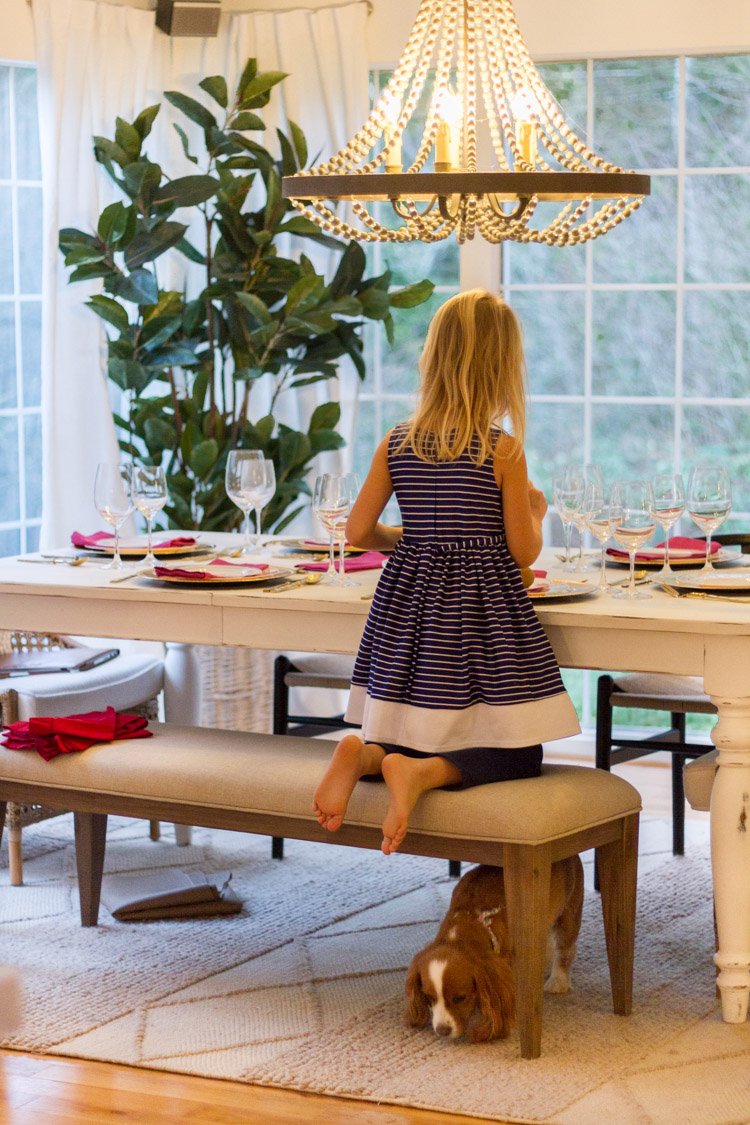 A little girl kneeling on the dining room table bench with a little dog underneath it.