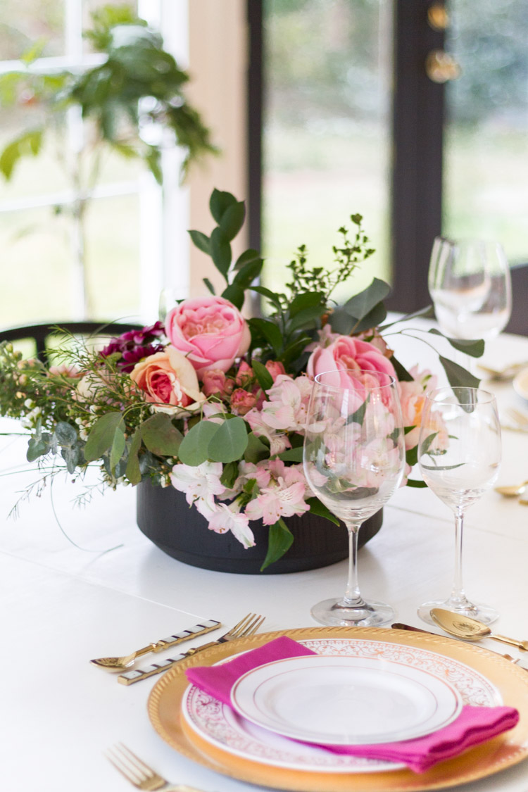 Pink flowers and greenery as the centerpiece on the table.