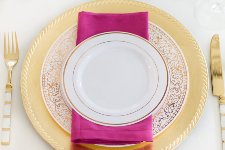 Ornate plates in gold and white on the able with gold knife and fork.