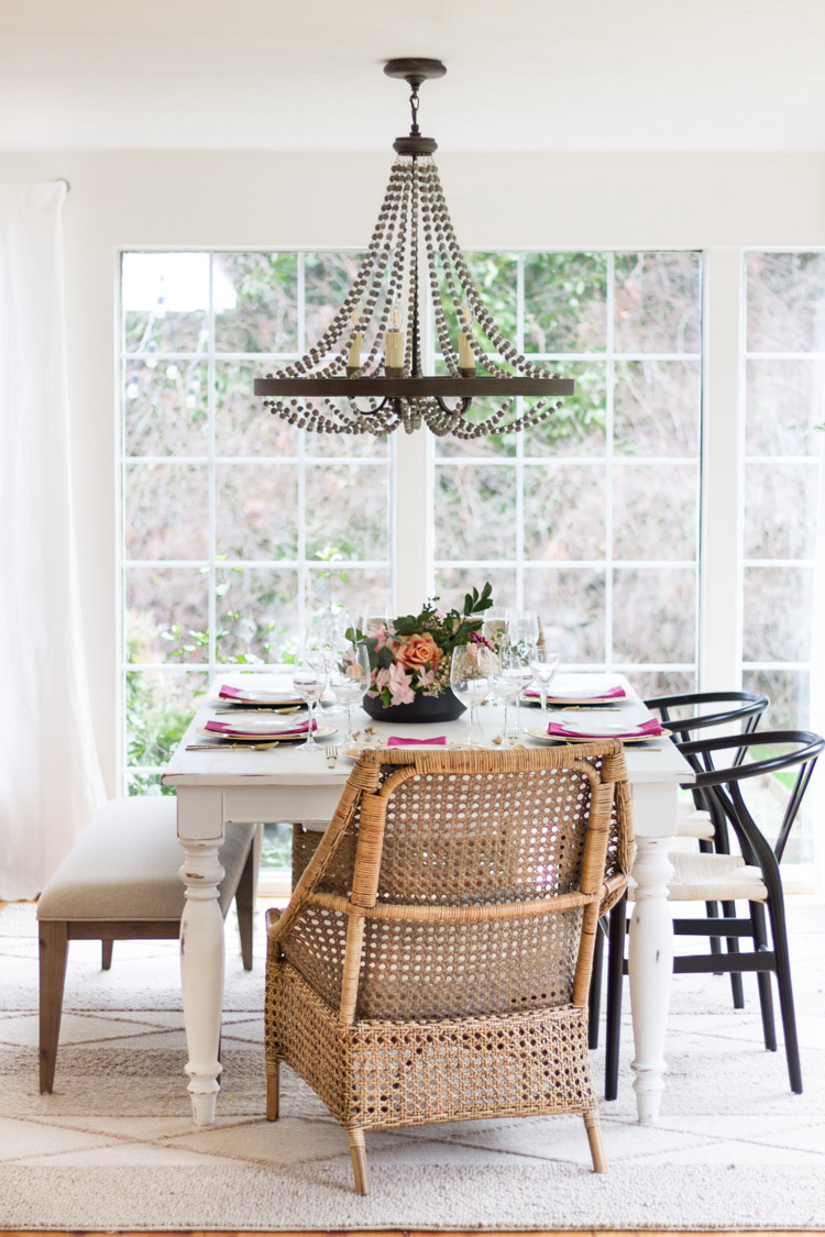Dining room table with large chandelier over top of it.
