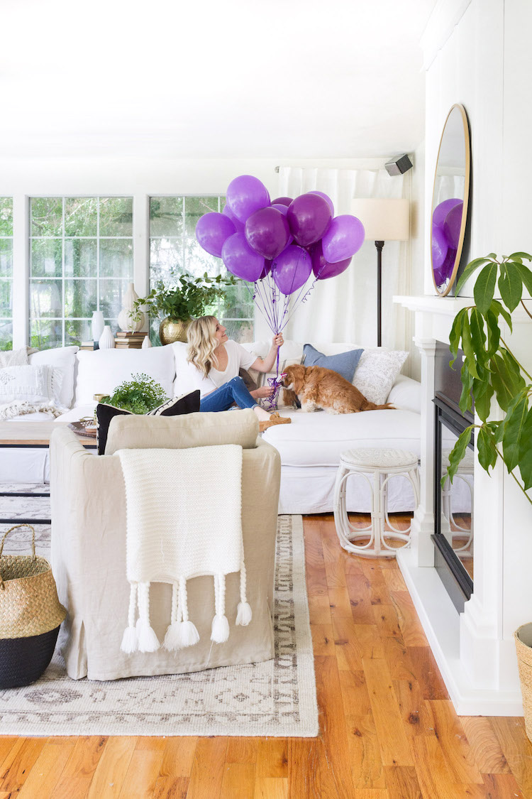 A woman sitting on a white couch with purple balloons in her hand.
